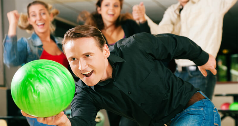 Image of a man bowling with friends cheering behind him