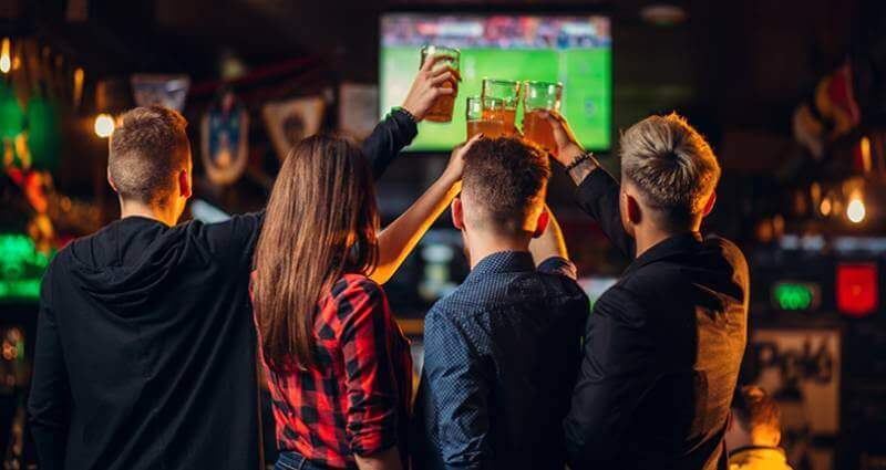 Image from behind of four people watching a television and raising beer glasses