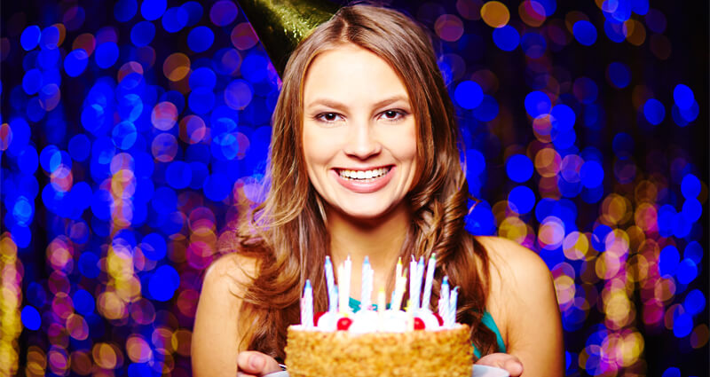 Image of a smiling woman holding a birthday cake