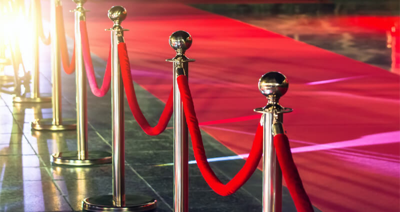 Image of stanchions with velvet ropes in front of a red carpet